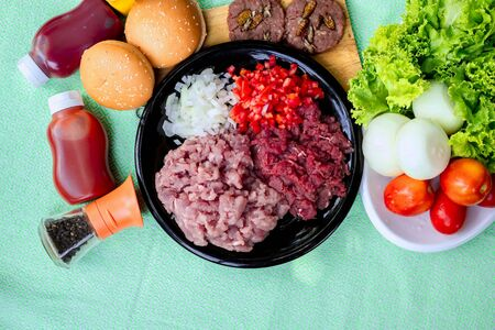 Homemade hamburger with beef or pork meat with lettuce and cheese, vegetables, sauce and placed on table Zdjęcie Seryjne