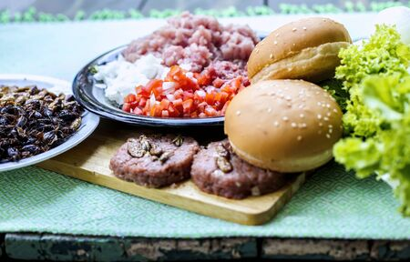 Homemade hamburger with beef or pork meat with lettuce and cheese, vegetables, sauce and french fries placed on old wooden table Zdjęcie Seryjne