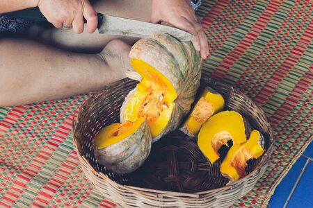 Cutting pumpkin on the basket