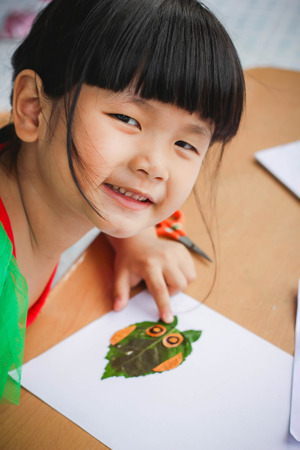 Lovely girl with leaves in the work of art , Children and art from the leaves. , Leaves on art , Cute little girl with Craft for kids,Crafts with kids , selective focus , Thailand.