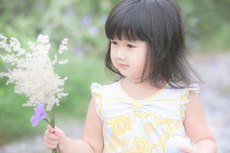 Happy asian little girl holding grass flower , Cute little asian girl and grass flower in her hand, Asian Thailand , Outdoor portrait. Imagens - 86628191