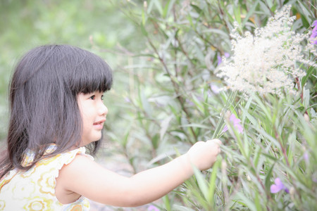 Happy asian little girl holding grass flower , Cute little asian girl and grass flower in her hand, Asian Thailand , Outdoor portrait. Imagens - 86628194