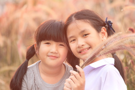 Two girls smiled brightly in the meadow , Asian Girl , Thailand. Imagens - 93211132