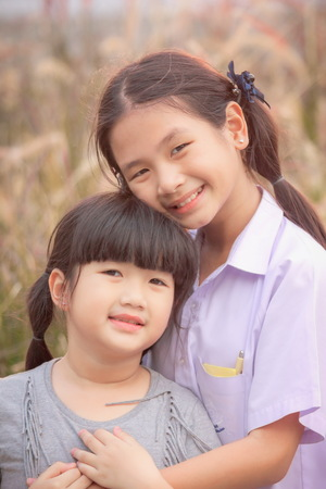 Two girls smiled brightly in the meadow , Asian Girl , Thailand. Imagens - 93211133