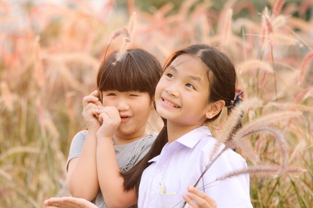 Two girls smiled brightly in the meadow , Asian Girl , Thailand. Stock Photo