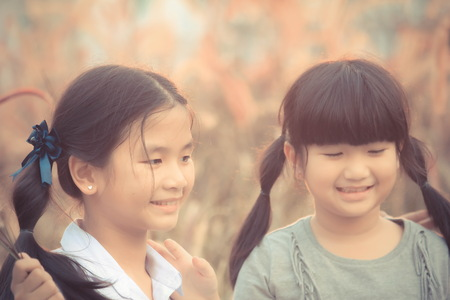 Two girls smiled brightly in the meadow , Asian Girl , Thailand. Imagens - 93212284