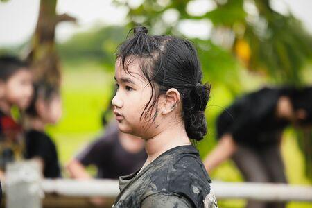 Asian girls playing in mud. Imagens