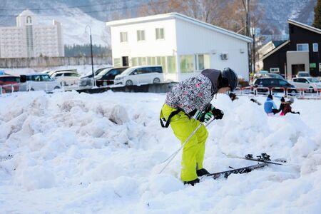 Asian men learn to ski on white snow