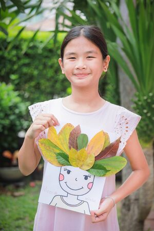 Lovely girl with leaves in the work of art Imagens