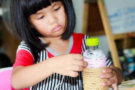 Asian girls making jobs D.I.Y. vase with used water bottles