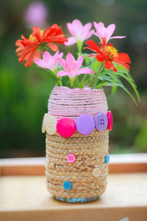 Asian girls making jobs D.I.Y. vase with used water bottles , A 6-year-old Asian child doing crafts D.I.Y. Flower Vases from Waste Materials , Crafts for kids Imagens