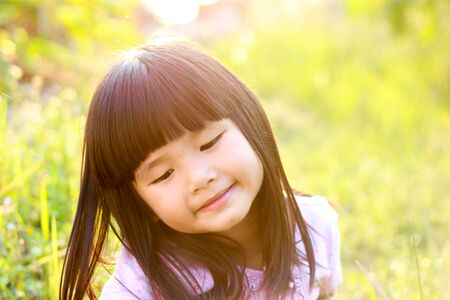 A little asian girl with a bright smile , Outdoor portrait , Thailand. Imagens