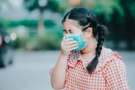 An Asian girl wearing a Corona protective mask , An Asian girl has a cough with phlegm. , Asian children wear medical masks to protect PM 2.5