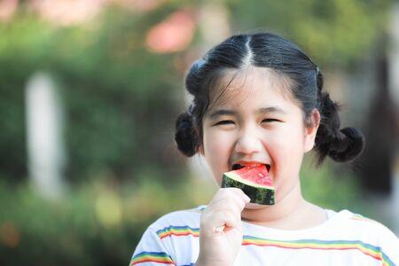 Asian girl eat watermelons with a bright smile