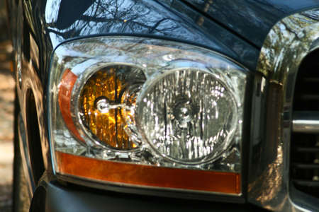 The headlight, signal, and part of a grill of a contemporary pick-up truck.