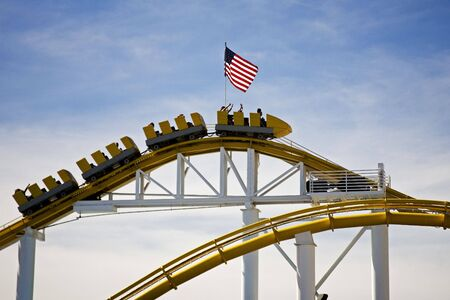 peaking: Roller Coaster peaking on track with flag on top