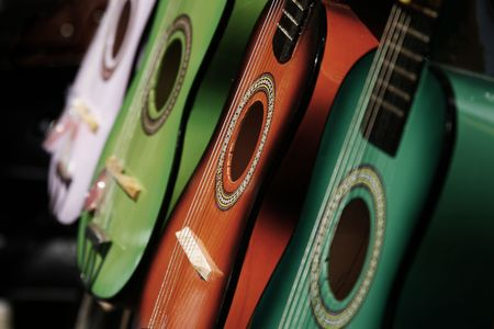 Row of colored acoustic guitars