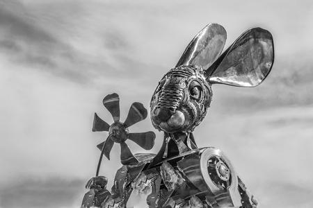 Metal rabbit sculpture holding flower
