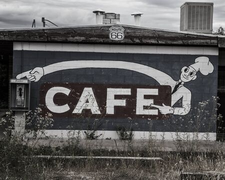 Abandoned cafe sign and payphone