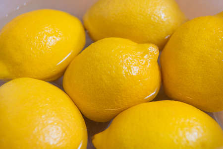 Fresh yellow lemons on a wooden background