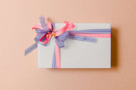Gift box tied with purple and pink ribbons on pink background