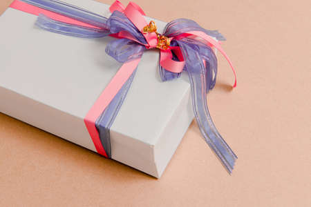 Gift box tied with  purple and pink ribbons on pink background Stock Photo