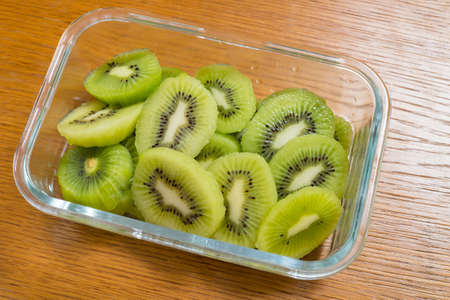 Many kiwi slices in a glass crisper on a wooden table.