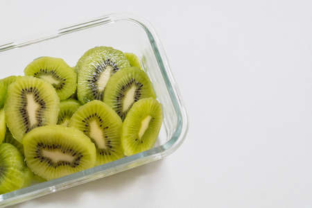 Many kiwi slices are placed in a glass crisper.