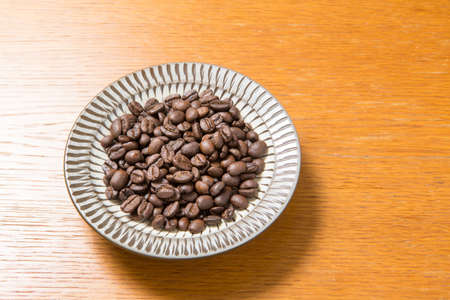 Coffee beans on a plate placed on a wooden table Zdjęcie Seryjne