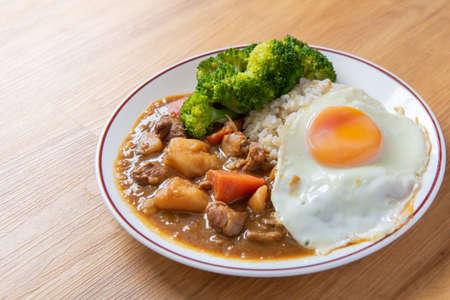 Chicken curry rice on wooden background (Poached egg, potato, enoki mushroom, onion, broccoli in Japanese style) Zdjęcie Seryjne