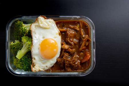 Arroz con carne al curry en lonchera de vidrio sobre mesa de comedor de madera negra (Onsen tamago, papa, hongo enoki, cebolla, brócoli, estilo japonés)