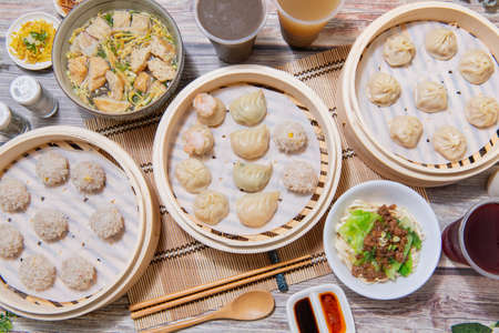 Steamed xiaolongbao and steamed dumplings served in a traditional steaming basket (close up) Фото со стока