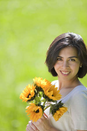 beautiful, young Hispanic woman in a grassy meadow holding flowers