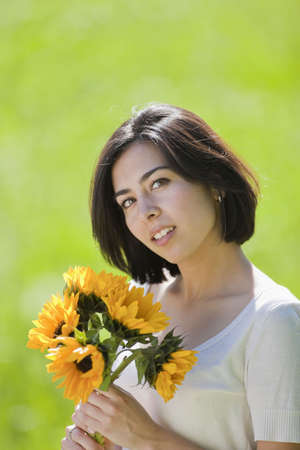 beautiful, young Hispanic woman in a grassy meadow holding flowers photo