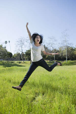 Hispanic girl jumping in a grassy field photo