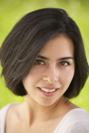 potrtait of a beautiful, young Hispanic woman in a grassy meadow photo