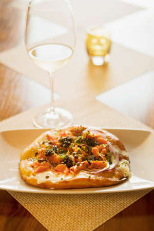 sauvignon blanc: maple-smoked salmon pizza with lemon creme fraiche and a glass of sauvignon blanc wine, Root 246 Restaurant, Solvang, California, United States of America Stock Photo