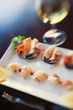 appetizer of local rock crab claws and a glass of chardonnay wine