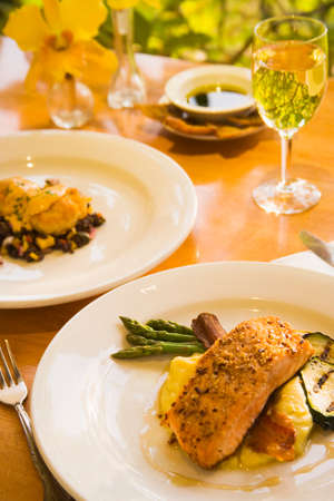 pecan: honey glazed and pecan crusted salmon, shrimp cakes and a glass of chardonnay wine Stock Photo