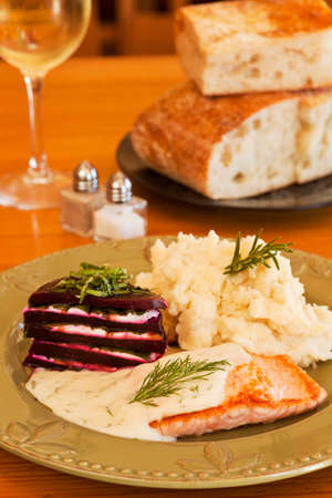 organic salmon in dill sauce with mashed potatoes and beets layered with goat cheese and basil served with white wine