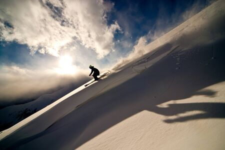 moving down: Freerider moving down a slope. Winter sunset in the mountains