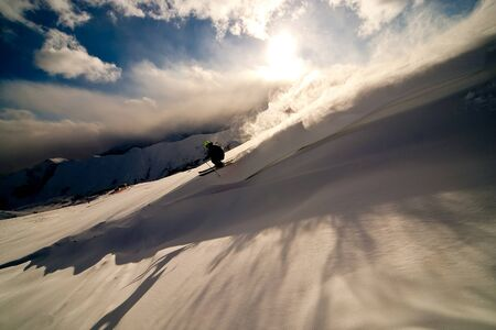 Freerider moving down a slope. Winter sunset in the mountains