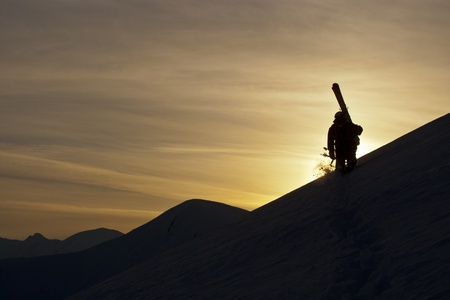 Skier on the background of sunset in the mountains