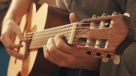 Hands of guitarist playing a guitar. Close up