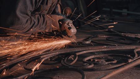 Gros plan des mains de l'homme lissant la grille métallique