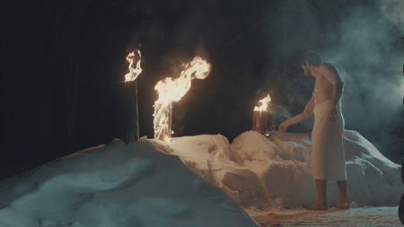 sauna nackt: A man after sauna, in a towel barefoot on the snow setting fire to the log.