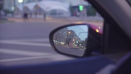 View of the city traffic in cars rearview mirror