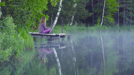 Young woman meditating on the shore of a lake