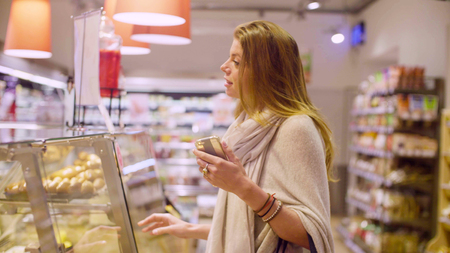 store shelf: Young attractive woman in a supermarket Stock Photo