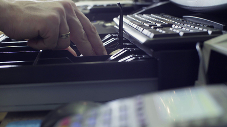 Close up man's hands putting money in cash box